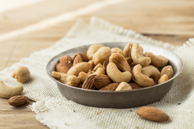 Mix nuts and dried fruits background and wallpaper. seen in top view of mix nuts and dried fruits in the bowl and wood spoon decorated with some nuts and green leaf on white wood in background. Premium Photo
