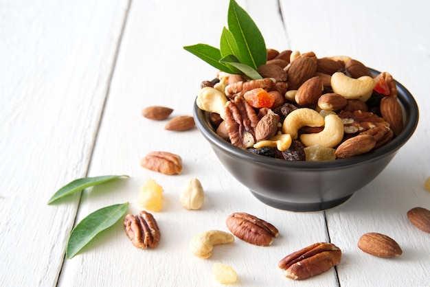 Mix nuts and dried fruits in the bowl put on the white painted wooden. Premium Photo