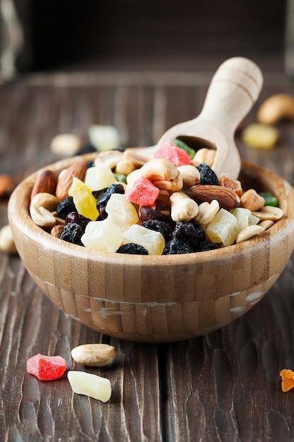 Микс из сушеных орехов и фруктов на деревянном столе Premium Фотографии