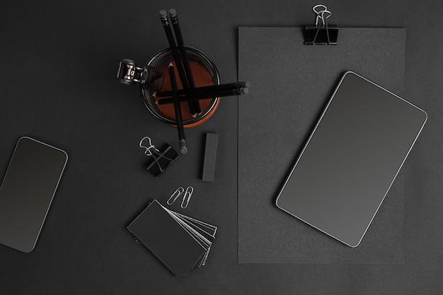 現代のオフィスの机の上の事務用品とビジネスガジェットのミックス。黒の背景に黒のオブジェクト。 Premium写真