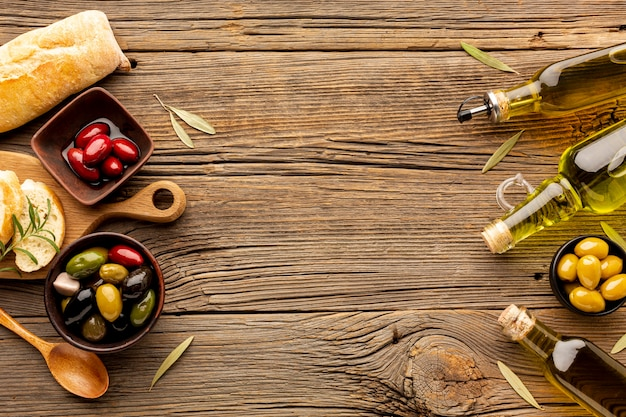 Mix of olives in bowls olive oil bottles and bread with copy space Free Photo