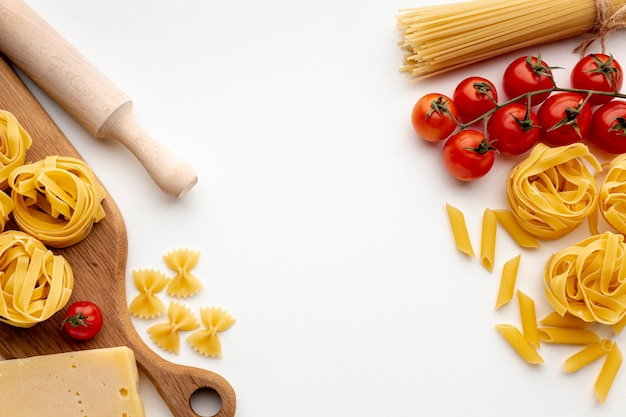 Mix of uncooked pasta with tomatoes and hard cheese Free Photo