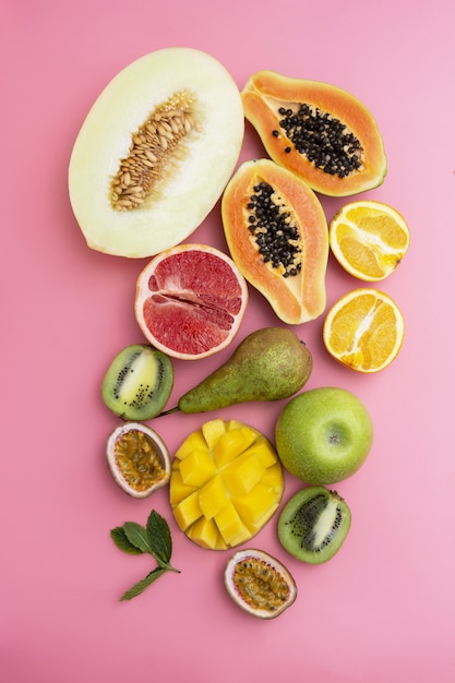 Mix of various exotic fruits. pink background. flat lay. Premium Photo