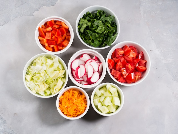 Mix of vegetable bowls for salad or snacks on gray background. diet detox concept Premium Photo