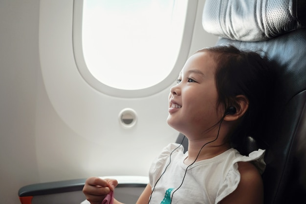 Mixed asian girl watching movie in flight, family traveling abroad with children Premium Photo