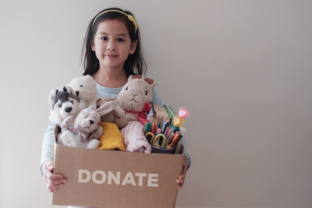 Mixed asian young volunteer girl holding a box full of used toys, cloths, books and stationery for donation Premium Photo