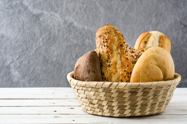Mixed bread in basket on white wooden table Premium Photo