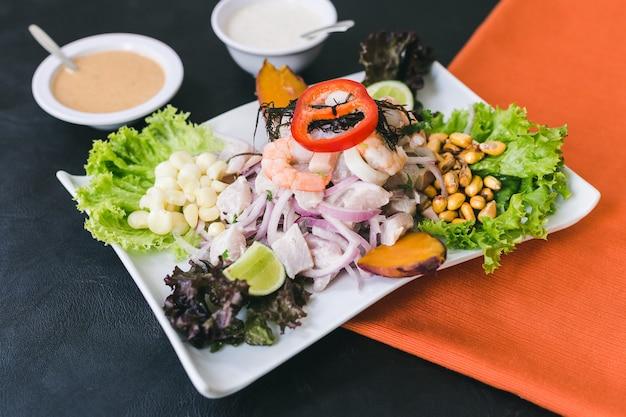 Mixed ceviche with peruvian sauce and garlic sauce Premium Photo
