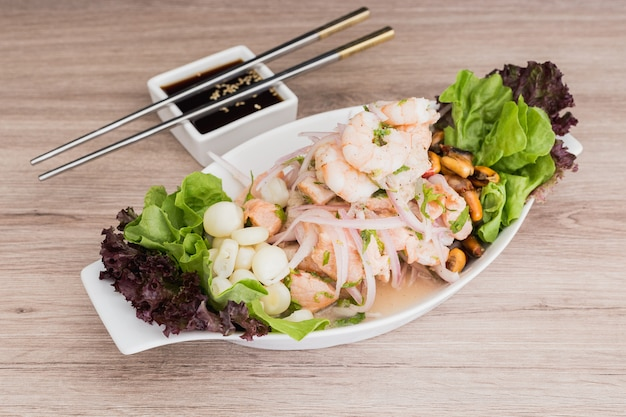Mixed ceviche with soy sauce on a wooden table Premium Photo