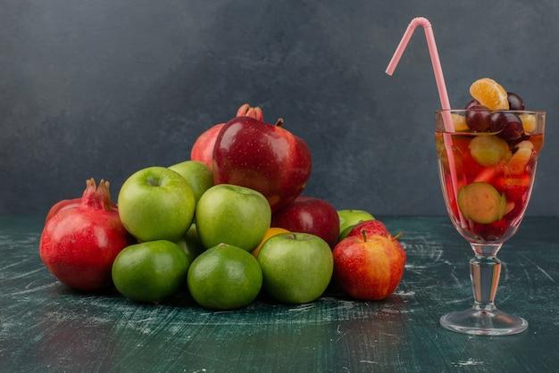 大理石のテーブルに新鮮な果物とジュースを混ぜたもの。 無料写真