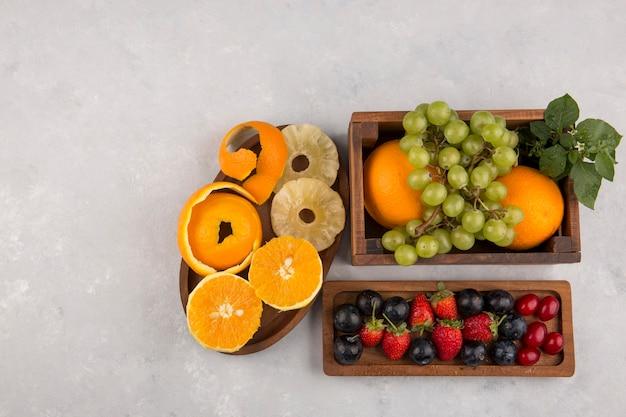 混合フルーツとベリーのホワイトスペースに木製の大皿 無料写真