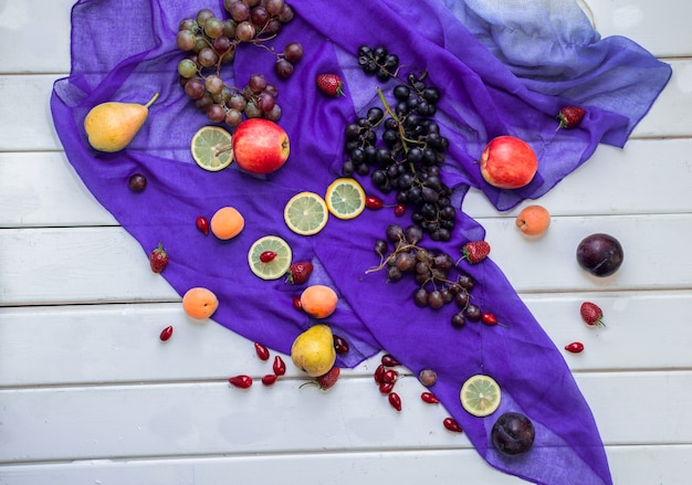 Mixed fruits on a violet ribbon on a white table. Free Photo
