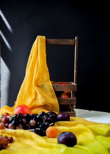 Mixed fruits on a yellow ribbon on a white table and fruit basket around. Free Photo