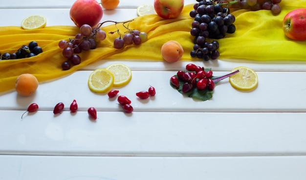 Mixed fruits on a yellow scarf on a white table, corner view. Free Photo