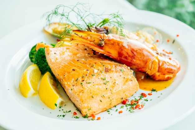 Mixed grilled seafood steak with salmon prawn and other meat Free Photo