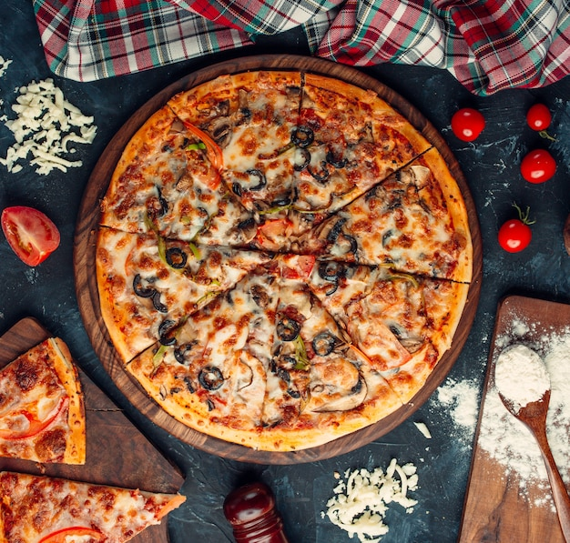 Mixed ingredient pizza with cheese and tomatoes. Free Photo