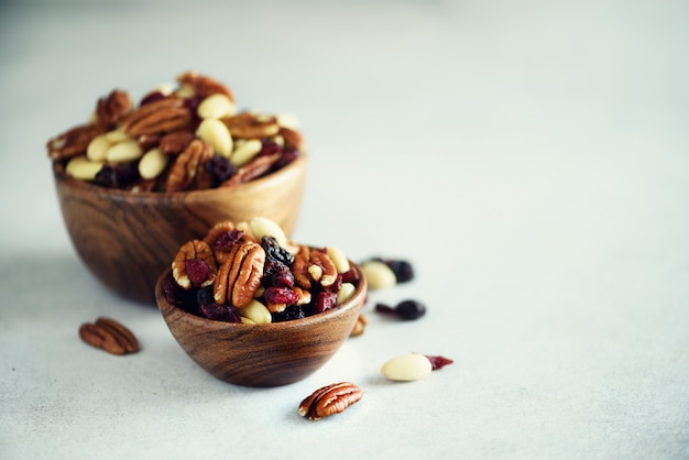 Mixed nuts and raisins in wooden bowl. Premium Photo