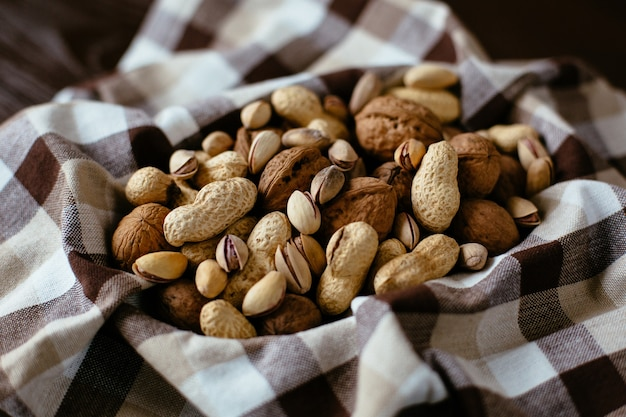 Mixed nuts on towel. group of different nuts: peanut, pistachio, walnuts. organic nuts Free Photo