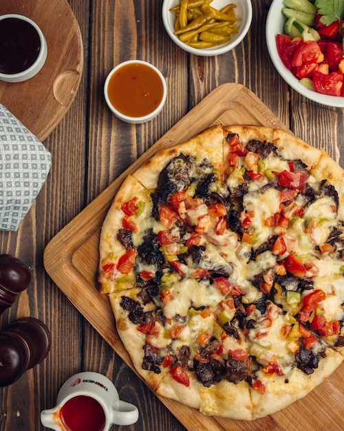 Mixed pizza with meat, tomato, bell pepper Free Photo