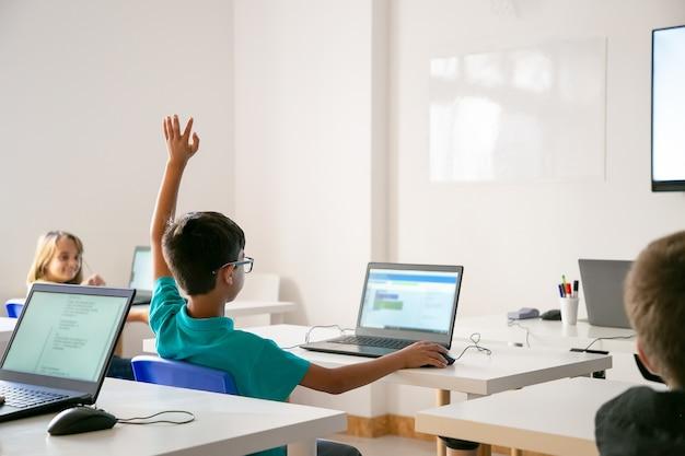 Мальчик смешанной расы в очках поднимает руку для ответа во время урока Бесплатные Фотографии