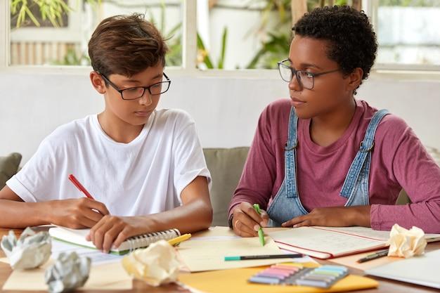 I compagni di classe di razza mista studiano insieme, scrivono su un taccuino, riscrivono le informazioni dai giornali, si preparano per l'esame scolastico, indossano abiti casual, posano al desktop, trascorrono del tempo insieme. persone, concetto di assistenza Foto Gratuite