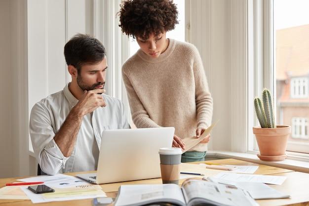 Семейная пара смешанной расы изучает документы, спрашивает друг друга, позируют на фоне уютного домашнего интерьера у окна, используют портативный компьютер, пьют кофе на вынос. Бесплатные Фотографии