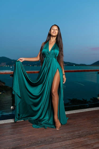 Mixed race girl with long black hair posing in an aquamarine evening dress. Premium Photo