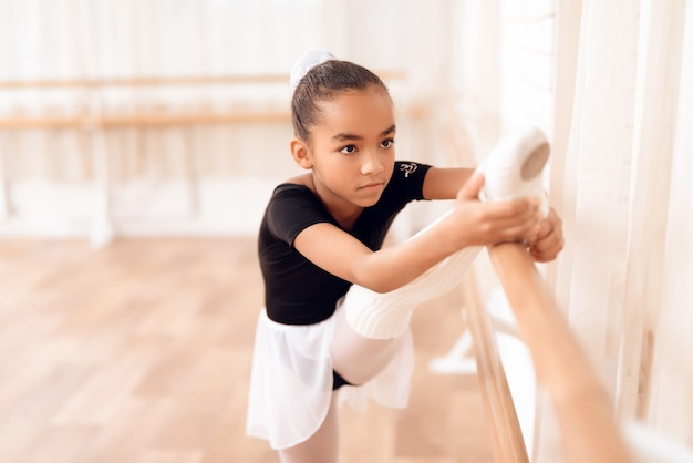 Mixed race kid is stretching near ballet bar. Premium Photo