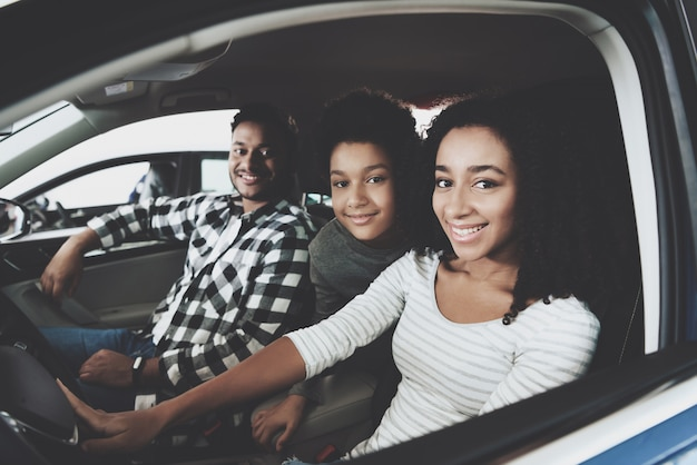 Mixed race marriage and kid family buying car. Premium Photo
