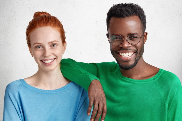 Free Photo | Mixed race relations concept. delihghted happy black and white  female and man wear bright sweaters, pose together against white
