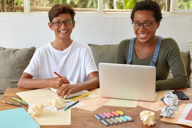 高校の混血の学生は、共同作業スペースで一緒に学び、ラップトップコンピューターでトレーニングのウェビナーを視聴し、スパイラルノートに記録を書き、創造的な解決策を見つけ、歯を見せる笑顔を持っています。 無料写真