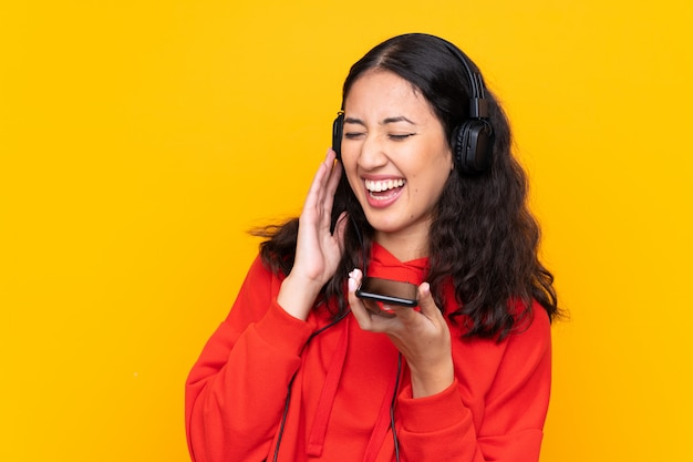 Mixed race woman wearing a red sweatshirt listening music with a mobile and singing Premium Photo
