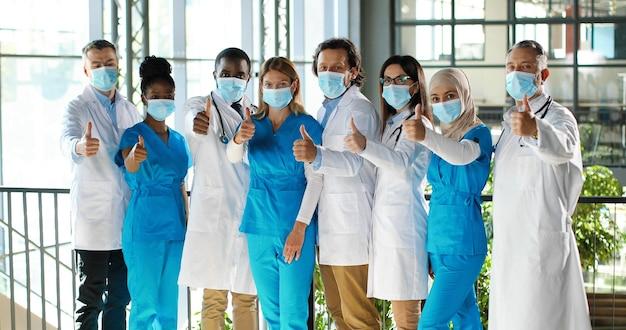 Смешанная бригада специалистов, мужчин и женщин-врачей в больнице. международная группа медиков в медицинских масках. защищенные рабочие, показывая большие пальцы на камеру. многонациональные врачи и медсестры Premium Фотографии