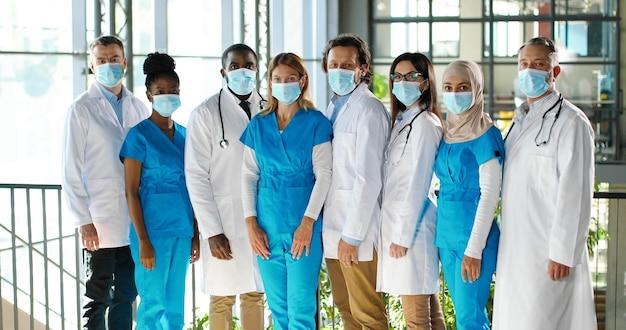 Смешанная бригада специалистов, мужчин и женщин-врачей в больнице. международная группа медиков в медицинских масках. защищенные рабочие. многонациональные врачи и медсестры в униформе в клинике. Premium Фотографии