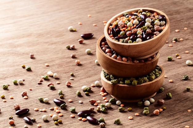 Mixed raw dried indian legumes in wooden bowls on rustic background with copyspace. Premium Photo