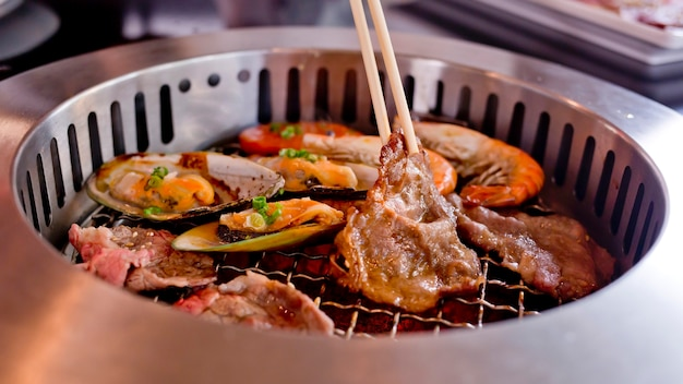 Mixed roasted meat and seafood and chopsticks on the bbq grill on roast. Premium Photo