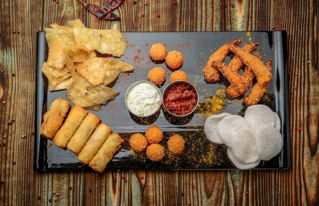 Смешанная закуска с чипсами, сыром и креветками в кляре Premium Фотографии