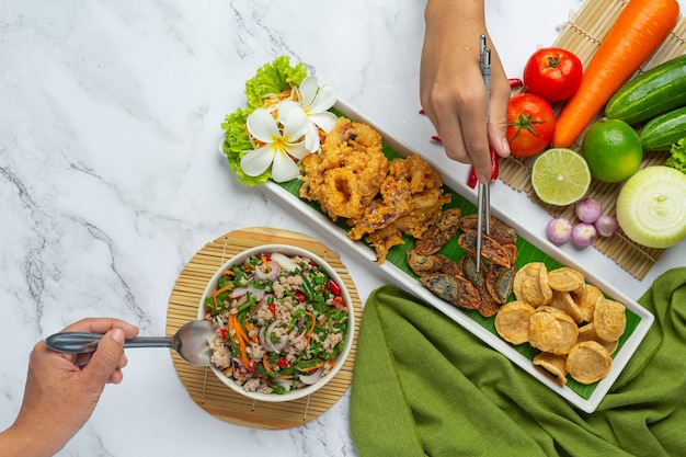 Mixed spicy salad with vietnamese sausage, preserved egg and crispy squid, thai food. Free Photo