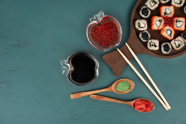 파란색 표면에 초밥 접시, 간장, 빨간 캐 비어를 혼합 무료 사진