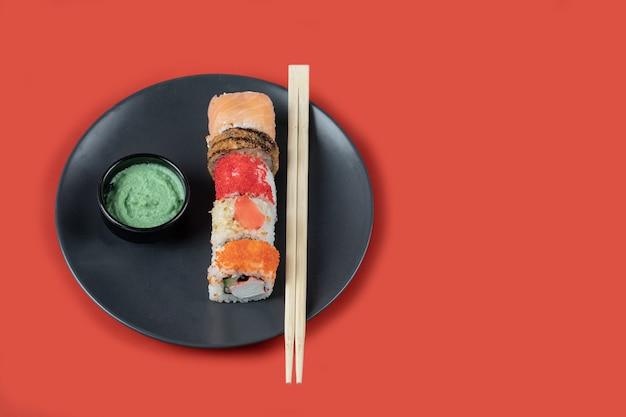 Rotoli di sushi misti in un piatto nero con bacchette e salse. Foto Gratuite