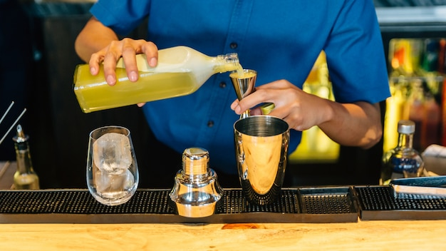 Mixologist making yuzu cocktail with shaker, double size jiggers and drinking glass Premium Photo