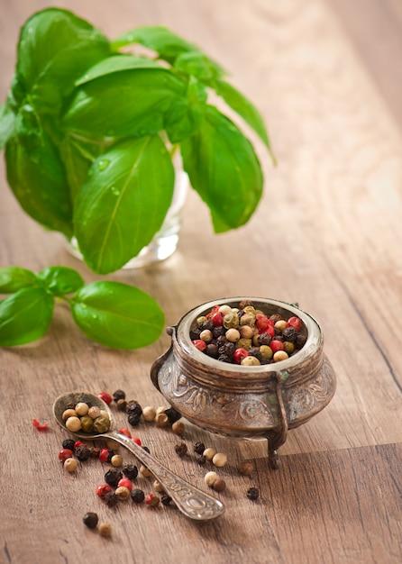 Смесь гороха перца в старой миске и листьев базилика Premium Фотографии