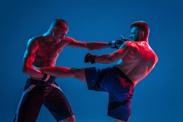 Mma. due combattenti professionisti punzonatura o boxe isolati sulla parete blu in neon Foto Gratuite