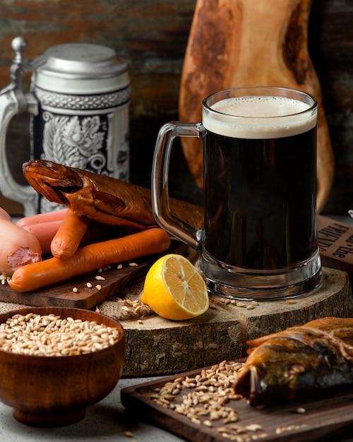魚のmo製とソーセージと黒ビール 無料写真