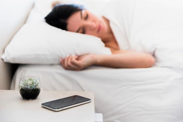 ベッドで寝ている若い女性の近くのベッドサイドテーブルの上の携帯電話とサボテンの植物 Premium写真