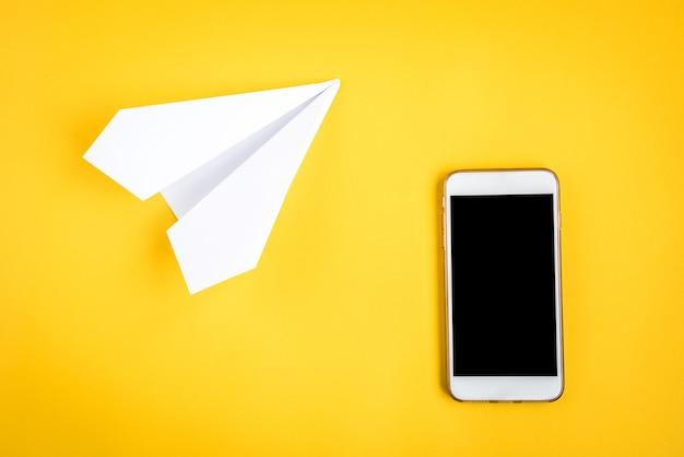 노란색에 휴대 전화와 종이 비행기 프리미엄 사진