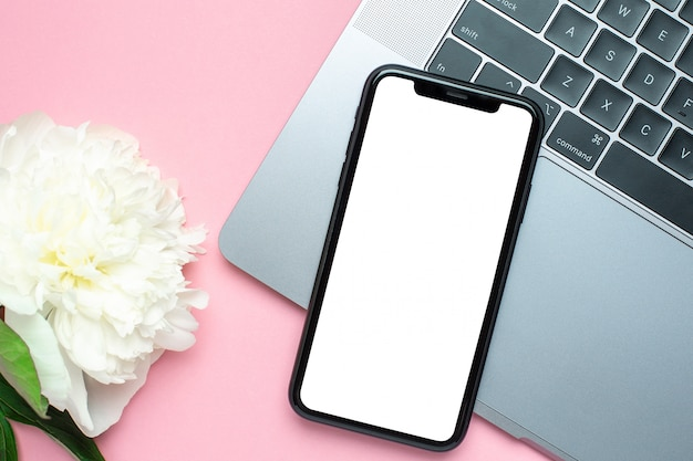 Mobile phone blank screen , laaptop and flower on pink   with copy space Premium Photo