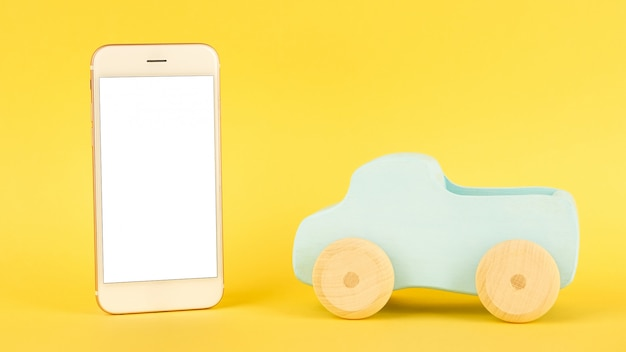 Mobile phone and children's blue toy car Premium Photo