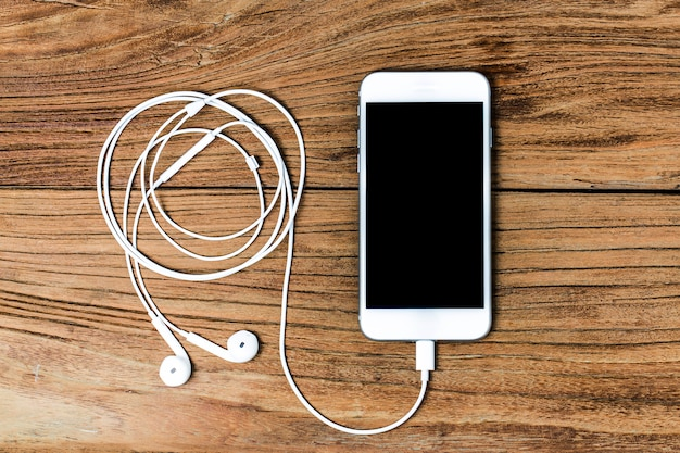 Mobile phone and earphones on wooden background Free Photo