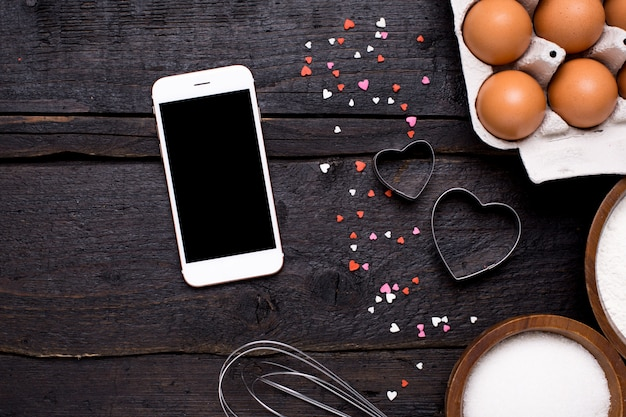 Mobile phone , kitchen tools and hearts on wood Premium Photo